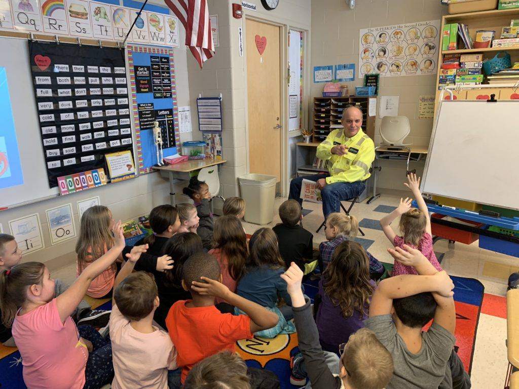 Plant manager Drew Schneider reads to 2nd graders at Niles Primary